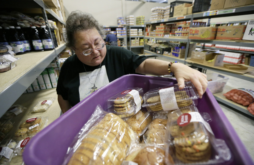 Volunteer Peggy Bragg of Des Moines, Iowa, unloads donated baked goods at the Des Moines Area Religious Council food pantry in Des Moines, Iowa. Because of rising demand, some charities are reducing the amount of food they offer each family.