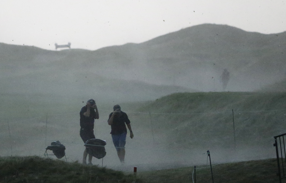 Fans scramble for cover from a storm that caused play to be suspended Friday before the second round had been completed. Play will resume at 7 a.m. Saturday.