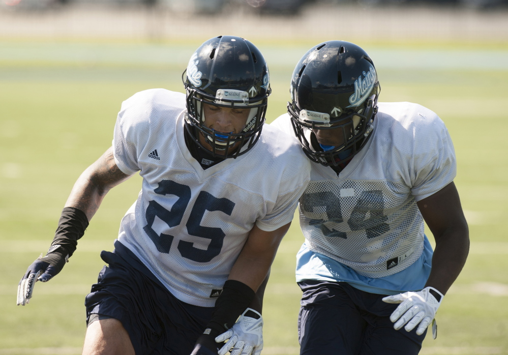 UMaine safeties Darrius Hart, left, and Sinmisola Demuren work out during practice Thurday in Orono. Maine should have a strong defense – it ranked second in the Colonial Athletic Association last season – but lacks experience at safety.  Kevin Bennett photo