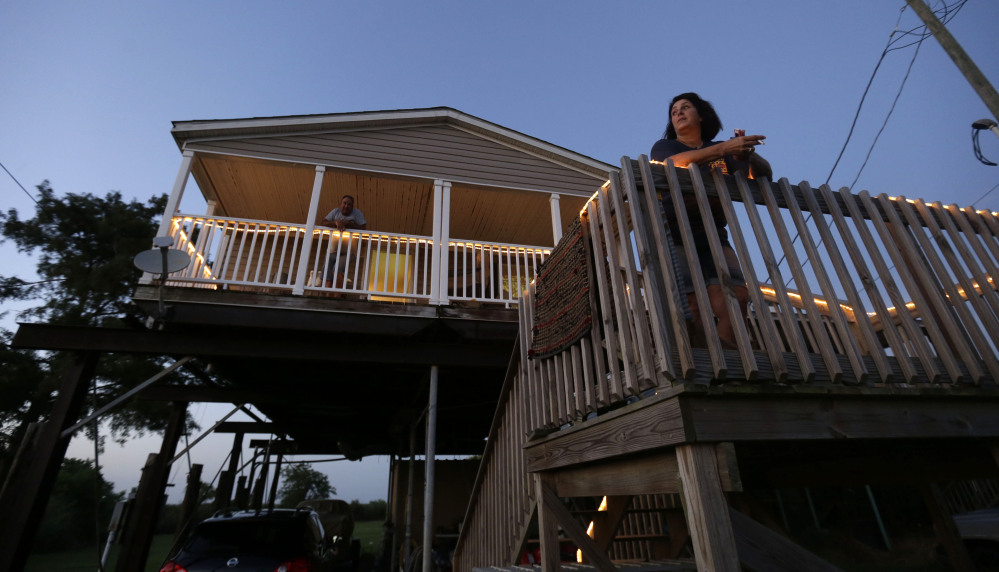 Rocky Morales and Suzanne Guidroz stand outside their home – rebuilt after the previous one was destroyed by Hurricane Katrina – in Delacroix, La., last week. Hurricanes speed up the disappearance of land and Morales, one of the few remaining fisherman to still call Delacroix home, knows that another Katrina could be the end of his town.