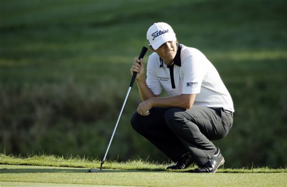 Matt Jones squats on the ninth hole during the second round of the PGA Championship golf tournament on Saturday. Jones finished his second round early in the morning and has a two-stroke lead.