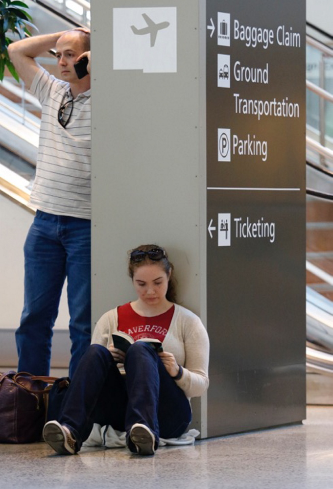 Carrie Kolar, right, reads as her boyfriend Matthew DiPrima, left, tries to make alternate travel plans to get home to Washington, D.C.,  from the Portland International Jetport on Saturday.