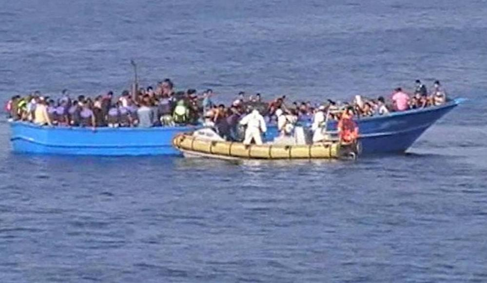 A boat carrying members of the Italian navy approaches a fishing boat crowded with migrants. Migrants brave the perilous Mediterranean crossing to seek asylum in Europe.
