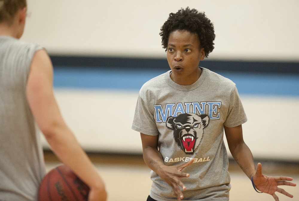 University of Maine women's basketball coach Edniesha Curry works out with student-athlete Liz Wood, far left, at the Memorial Gym recently. Wood said she was sold on Maine because of the vision coaches had for restoring pride in a program that had fallen on tough times.