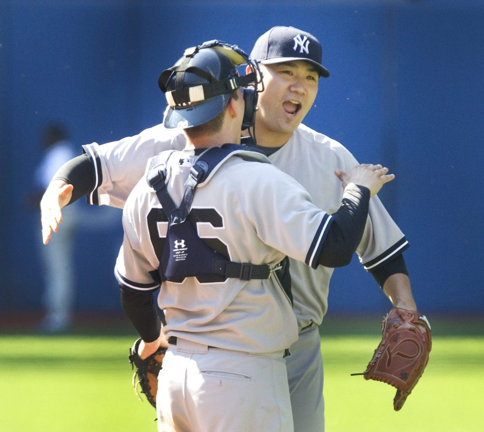 Yankees' starting pitcher Masahiro Tanaka embraces catcher John Ryan Murphy after finishing a five-hitter for a 4-1 victory at Toronto.