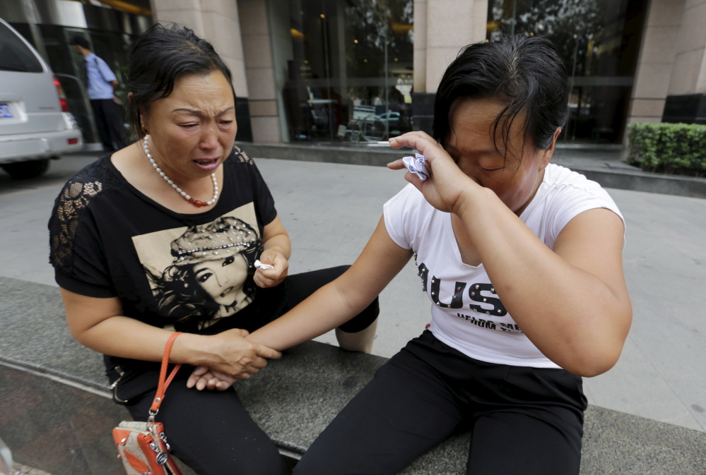 The mother of missing firefighter Dong Zepeng, right, wipes her face next to another family member as they cry outside the site of a news conference after demanding more information from government officials, following explosions Wednesday night in Tianjin, China. The death toll from two huge explosions that tore through an industrial area in Tianjin has risen to 112, the official Xinhua news agency said Sunday.