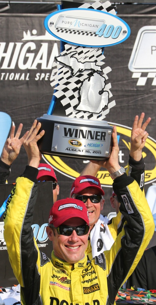 Matt Kenseth raises the winner's trophy after a victory that gave Joe Gibbs Racing five wins in the last six Sprint Cup races.