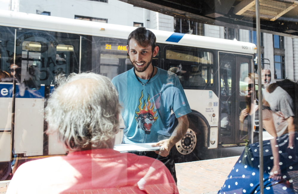 Daniel Sipe gathers signatures in August 2015 in support of a statewide minimum wage increase.  The Maine People's Alliance, which is trying to raise Maine's minimum wage to $12 an hour, has advertised for new workers at a rate closer to $10 an hour.