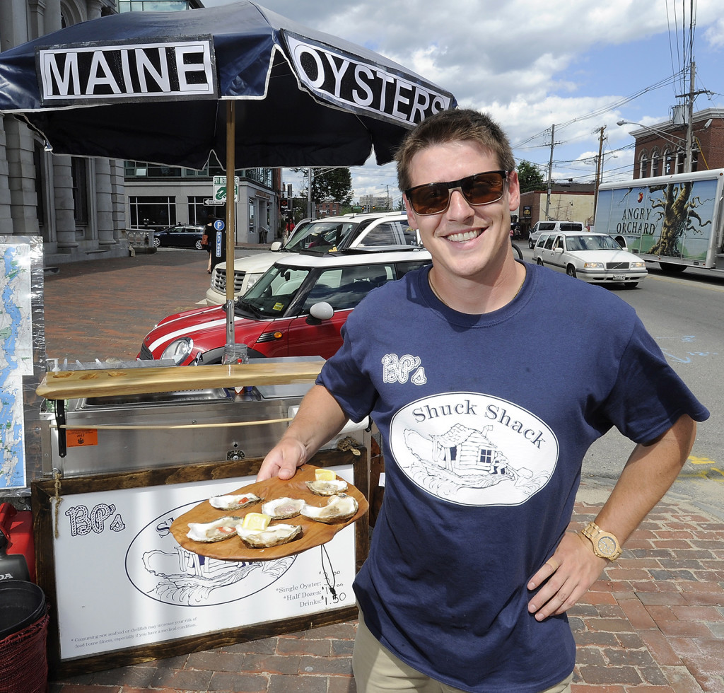 Brendan Parsons owner of  BP's Shuck Shack, presents a half-dozen oysters prepared in his food cart on Commercial Street. Gordon Chibroski/Staff Photographer