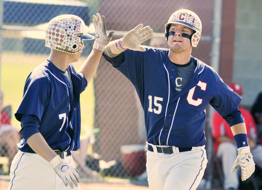 Sam Huston, right, exchanges a high-five with Trevor DeLaite after scoring a run for Coffee News in the American Legion baseball state championship game in South Portland on Sunday. Huston drove in six runs in Coffee News' 12-9 win over Morrill Post. John Ewing/Staff Photographer