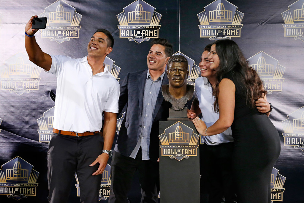 Children of former NFL player Junior Seau, from left, Jake, Tyler, Hunter and Sydney pose for a selfie with the bust of their late father, during inductions at the Pro Football Hall of Fame on Aug. 8 in Canton, Ohio.  The Associated Press