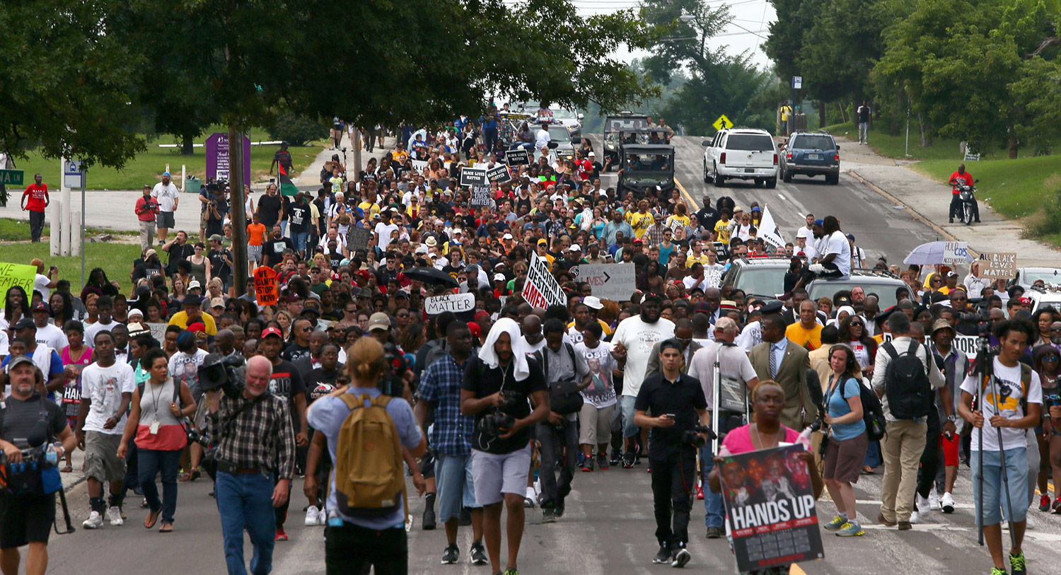 Led by Michael Brown Sr., people march along West Florissant Avenue from Canfield Green Apartments to Greater St. Mark Church Sunday, on the anniversary of the fatal shooting of Michael Brown Jr. by a Ferguson police officer.  The Associated Press