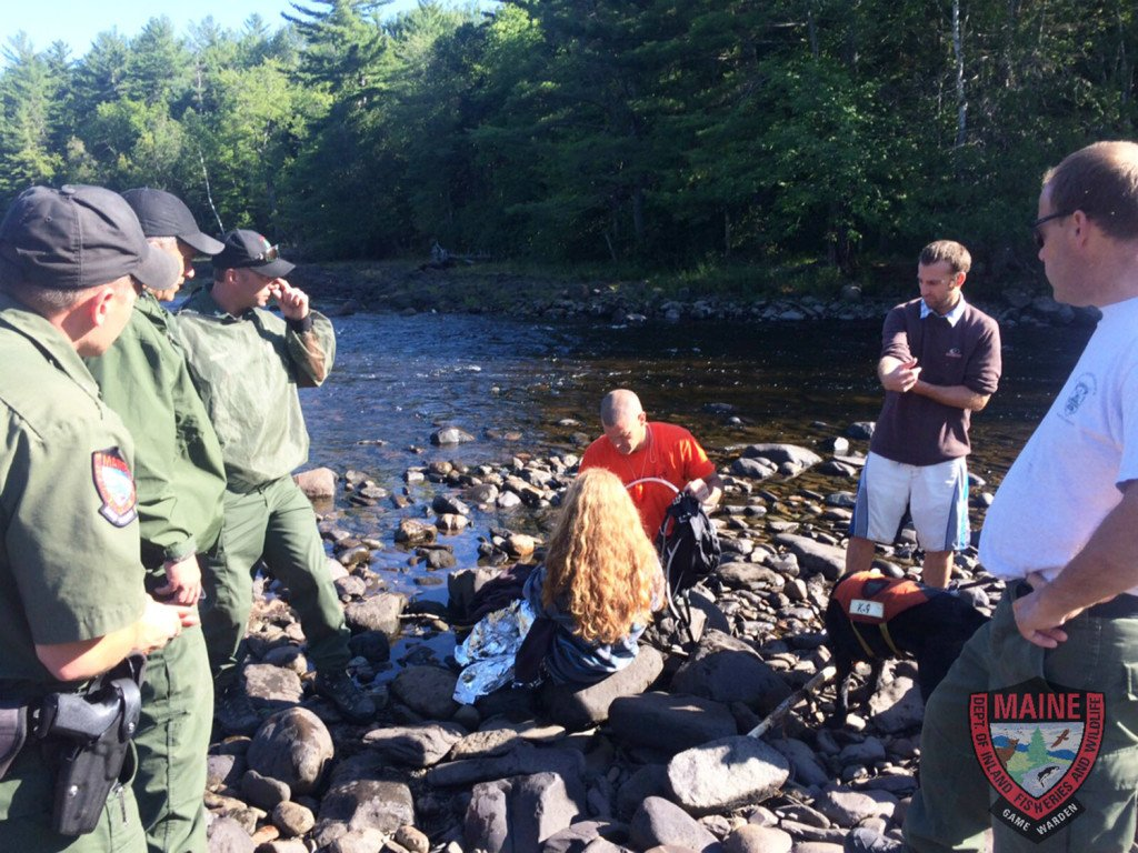 Tending to Erica LaChance, who is sitting, are Maine game wardens, from left, William Shuman, Tom McKenney and Jared Herrick, and Walter Glynn of the West Forks Fire Department, along with an unidentified acquaintance and Sgt. Chris Simmons, on Monday.