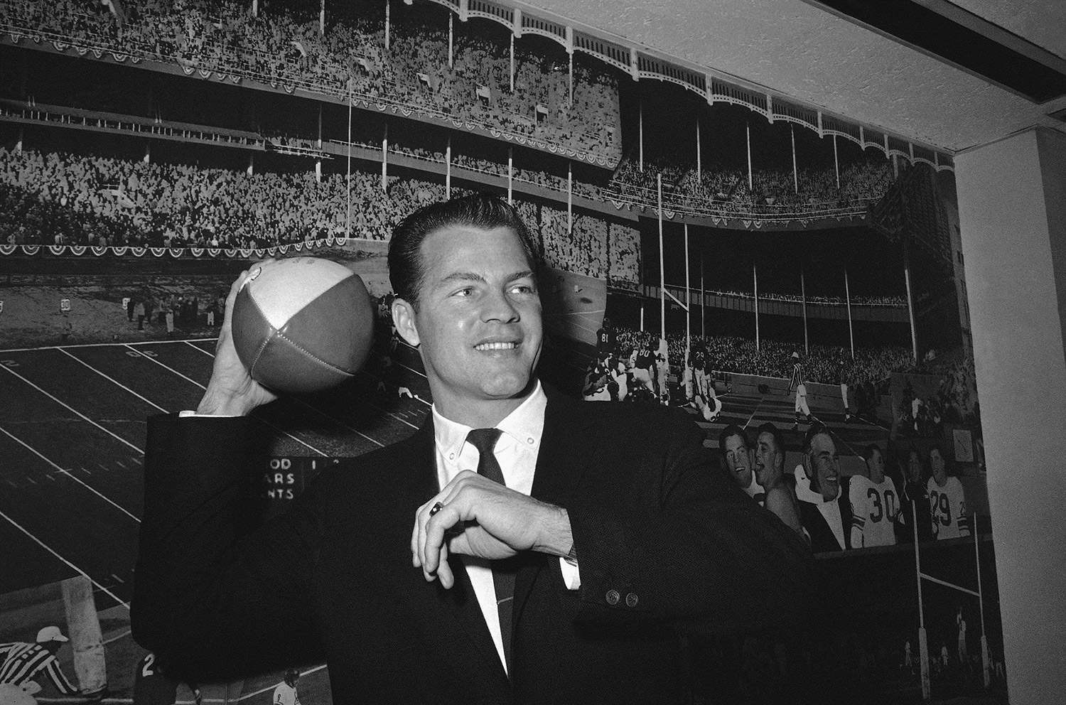 In this April 2, 1962 file photo, Gifford cocks his passing arm as he stands in front of photo mural of the Polo Grounds at the offices of the New York Giants in New York's Coliseum.
