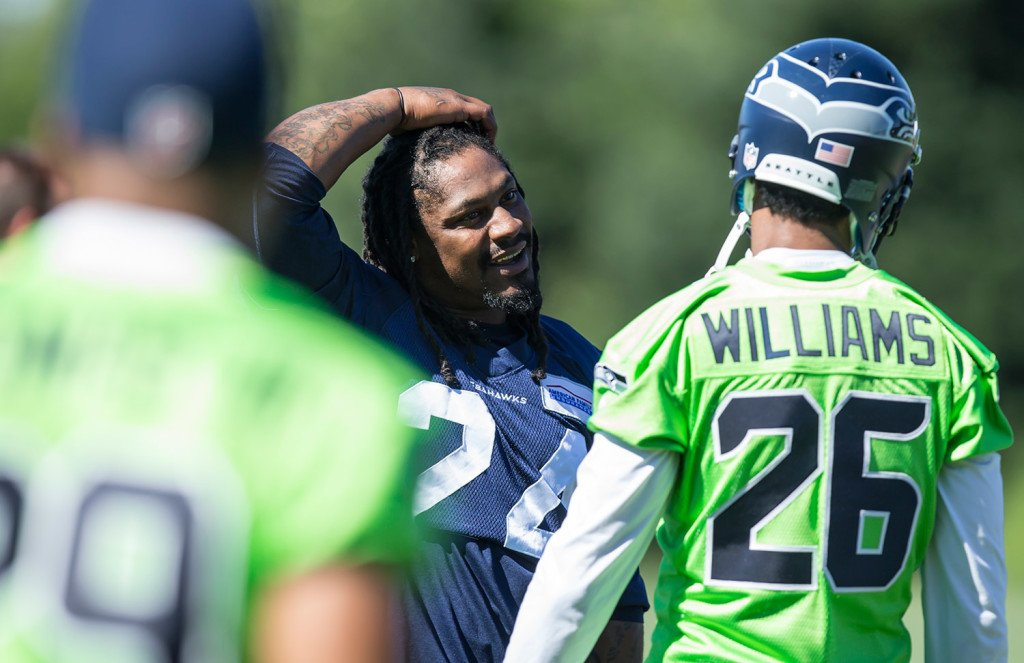 Seattle Seahawks running back Marshawn Lynch, center, talks to defensive back Cary Williams during an NFL football training camp on July 31 in Renton, Wash. The Associated Press