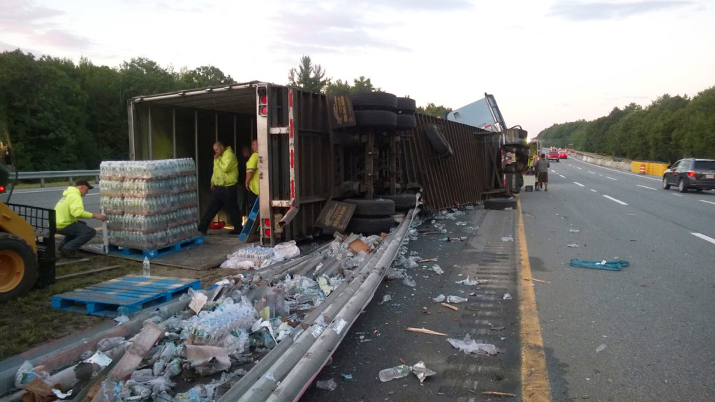 Crews unload a tractor-trailer full of Poland Spring water that overturned on the Maine Turnpike early Monday morning.