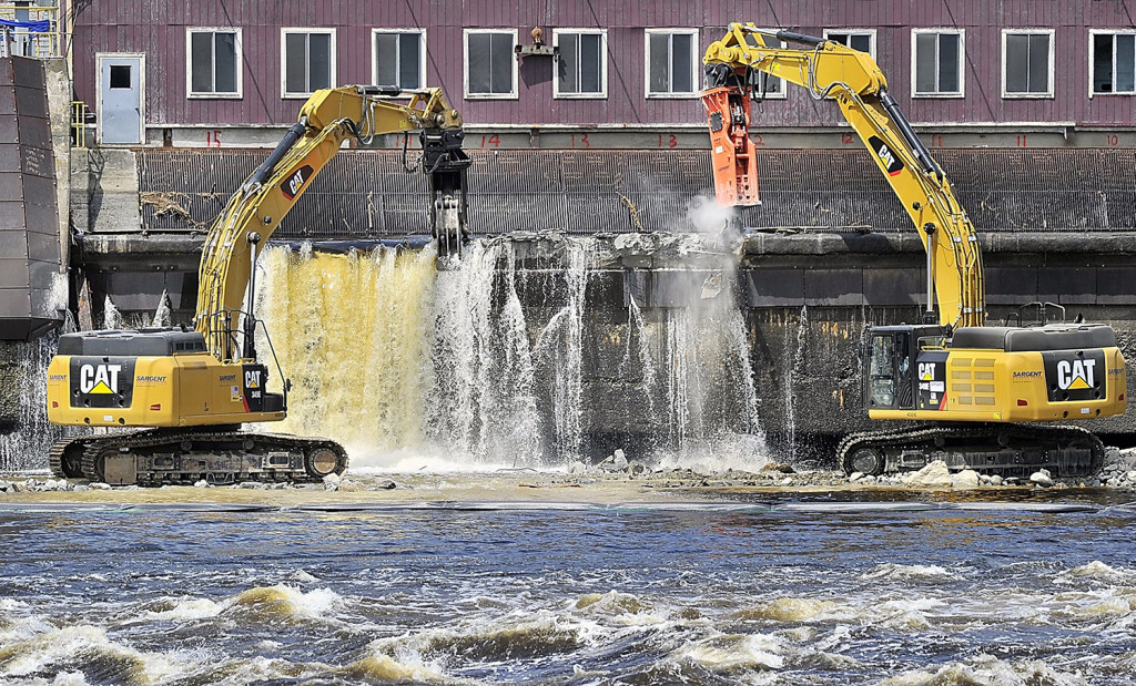 In this 2013 file photo, using excavators, construction workers breach the Veazie Dam in preparation for its removal on the Penobscot River in Orono, Maine. Gordon Chibroski/ Staff Photographer.