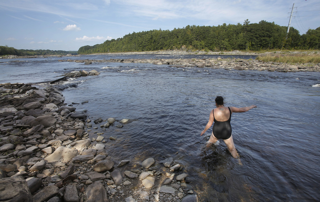 """Jan Sockbeson swims in the Penobscot River near where the Veazie Dam used to be. Sockbeson lives near the river and comes down often to explore and swim in the river. """"It's been great,"""" Sockbeson said. """"I'm learning so much about the river as I've been coming down here."""" Gregory Rec/Staff Photographer"""
