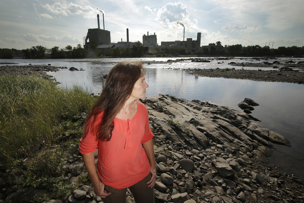 """Laura Rose Day, executive director of the Penobscot River Restoration Trust, stands on the side of the Penobscot River near where the Great Works Dam used to be. """"I really think the project represents people stepping outside of their silos and saying, 'Let's pretend for a minute that we can focus on what we all have in common,'"""" said Day. """"If people didn't do that, we wouldn't be standing here. We would be swimming."""" Gregory Rec/Staff Photographer"""