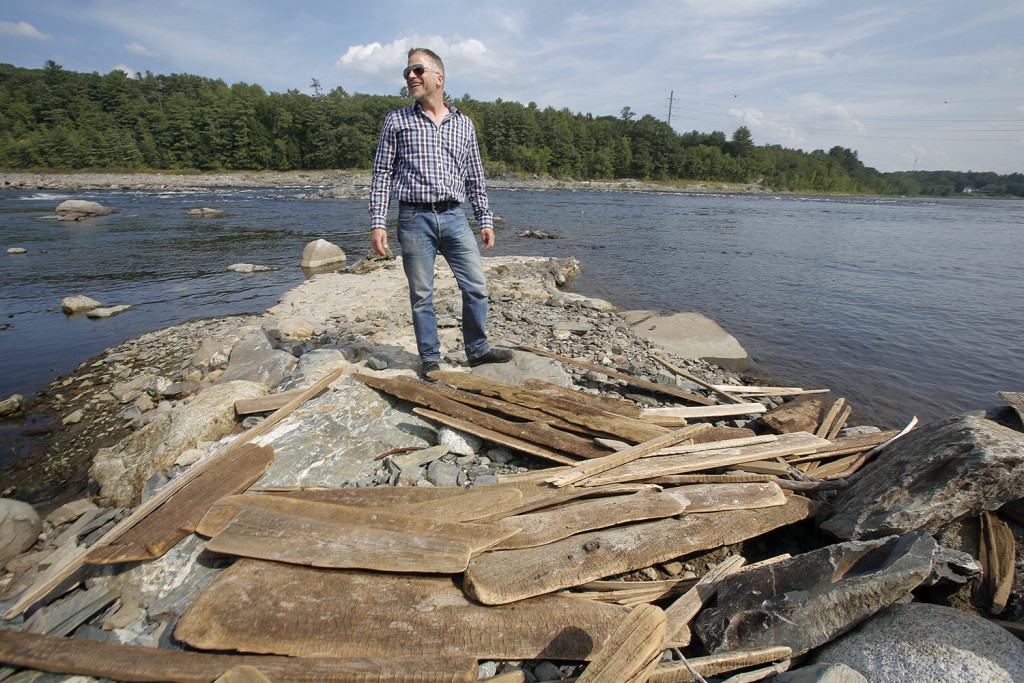 """Dan McCaw, a fisheries biologist with the Penobscot Nation's Department of Natural Resources, stands on a bank of the Penobscot River in Veazie where the Veazie Dam used to be. """"Unless you had been here before, it is hard to imagine,"""" McCaw said of the former dam. The timber slabs in the foreground are left over from the lumber mills that used to line the river many years ago. """"It's amazing stuff,"""" McCaw said. """"It is quite a connection to Maine's timber history."""" Gregory Rec/Staff Photographer"""