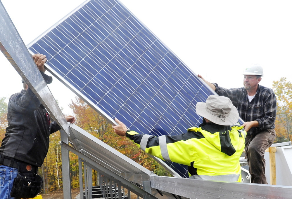 Workers install a solar electric panel in a ground-mounted solar array for Mt. Abram ski resort, similar to the solar array that is planned for a community solar farm in Wayne.