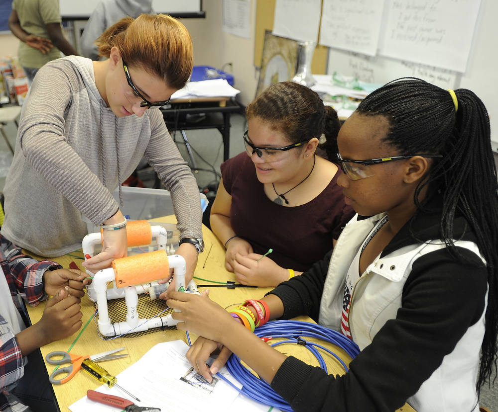 Audrey Watson, 11, left, helps her  classmates attach the wires to the motors on their submersibles.