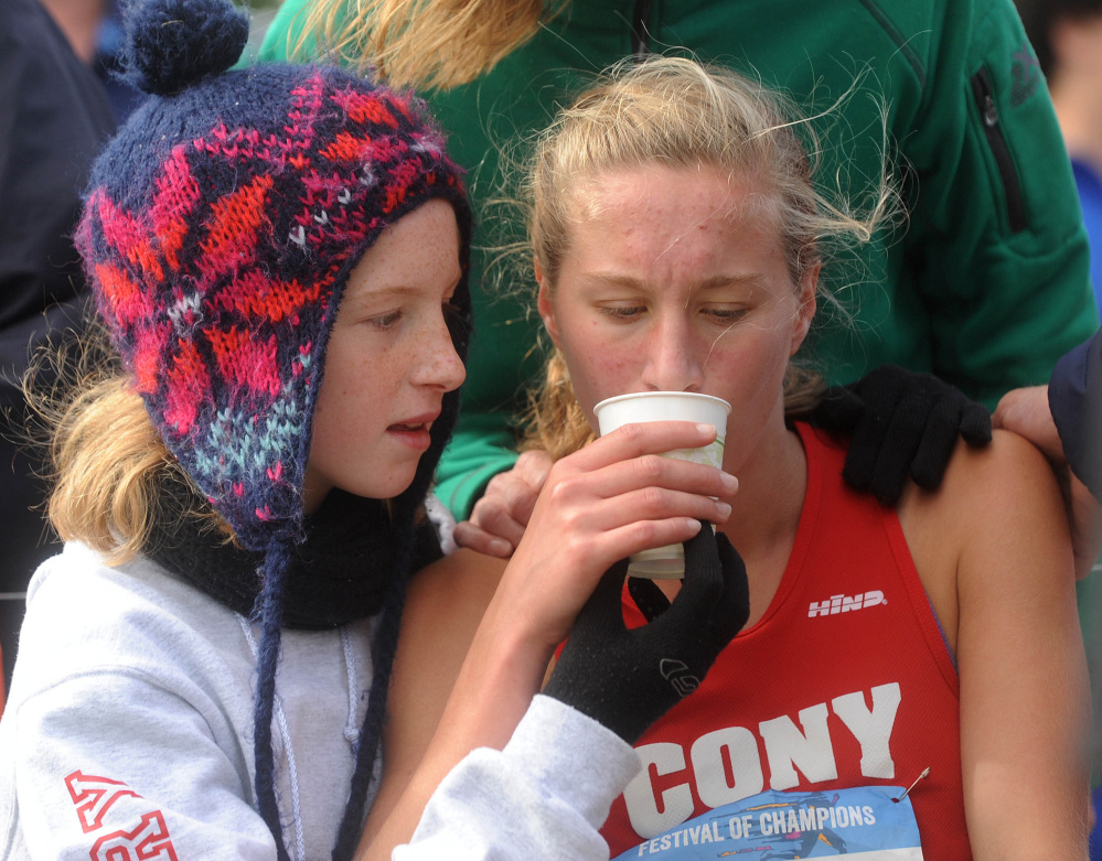 Anne Guadalupi of Cony High in Augusta drinks some water after finishing her race.