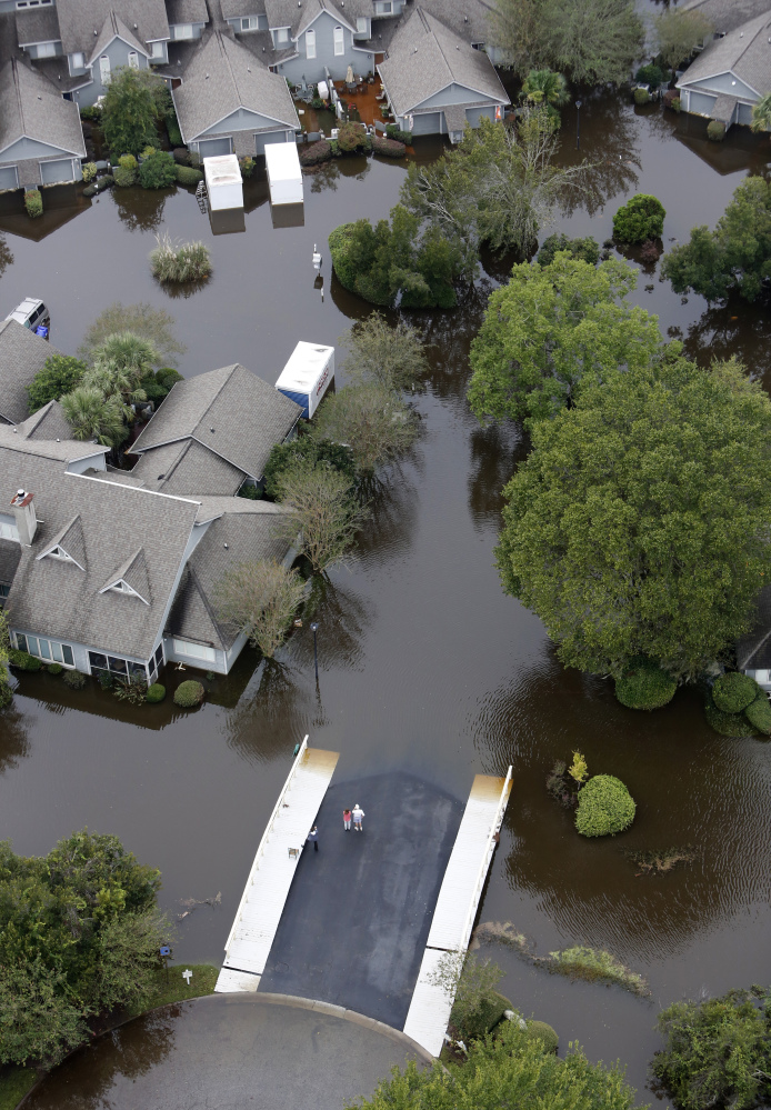 People stand on the safety of a bridge as homes sit in floodwater in a subdivision west of the Ashley river in Charleston, S.C., on Monday.