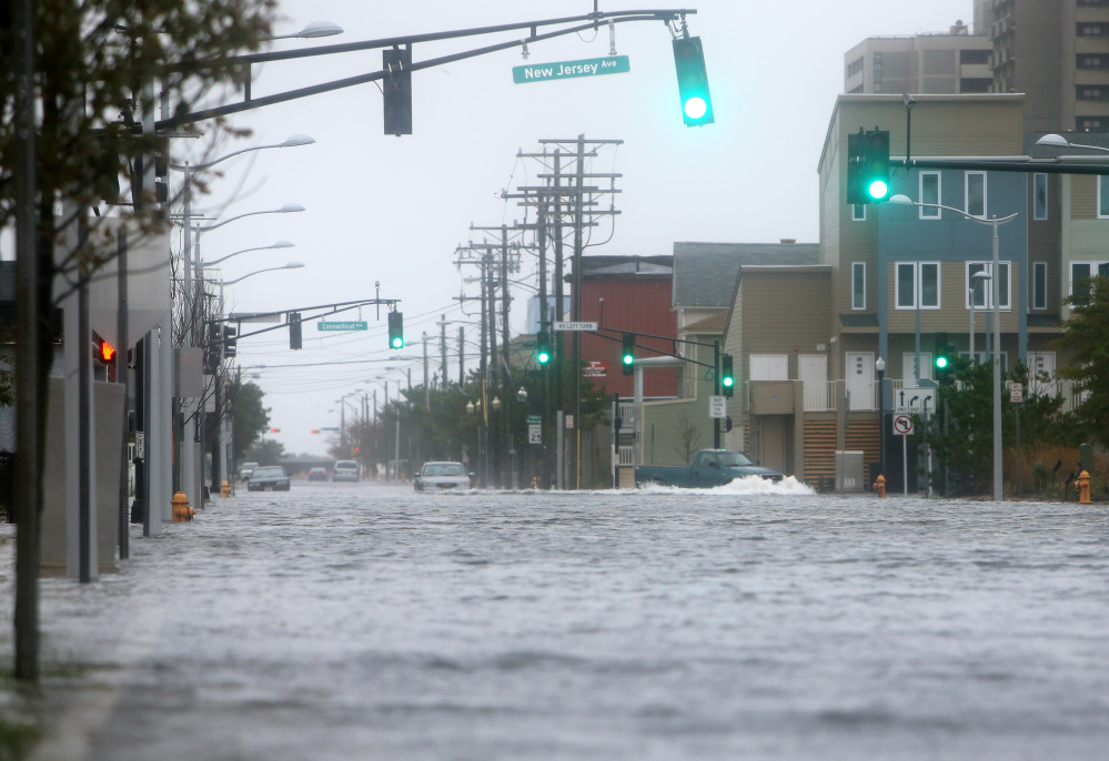 Cars make their way down a flooded street in Atlantic City, Saturday, Oct. 3, 2015. A coastal flood warning for the state is due to remain in effect until Sunday evening.