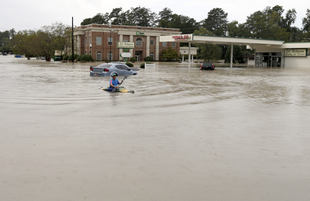 Jordan Bennett, of Rock Hill, S.C., paddles down a flooded a street in Columbia, S.C., Sunday, Oct. 4, 2015. The rainstorm drenching the U.S. East Coast brought more misery Sunday to South Carolina, cutting power to thousands, forcing hundreds of water rescues and closing many roads because of floodwaters.