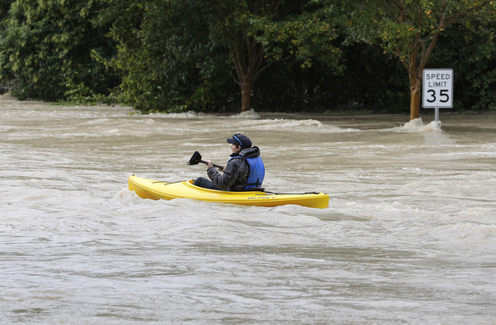 A man paddles a kayak down a flooded street in Columbia, S.C., Sunday, Oct. 4, 2015. The rainstorm drenching the U.S. East Coast brought more misery Sunday to South Carolina, cutting power to thousands, forcing hundreds of water rescues and closing many roads because of floodwaters.