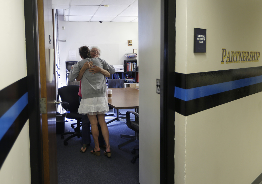 In the police station in Gloucester, Mass., in July, volunteer Ruth Cote, facing camera, hugs a participant in the Angel program, which refers drug addicts to treatment instead of prosecuting them. It's reportedly helped nearly 200 people embark on substance-abuse recovery in Massachusetts, but will it work in Maine, a state with far fewer treatment resources?