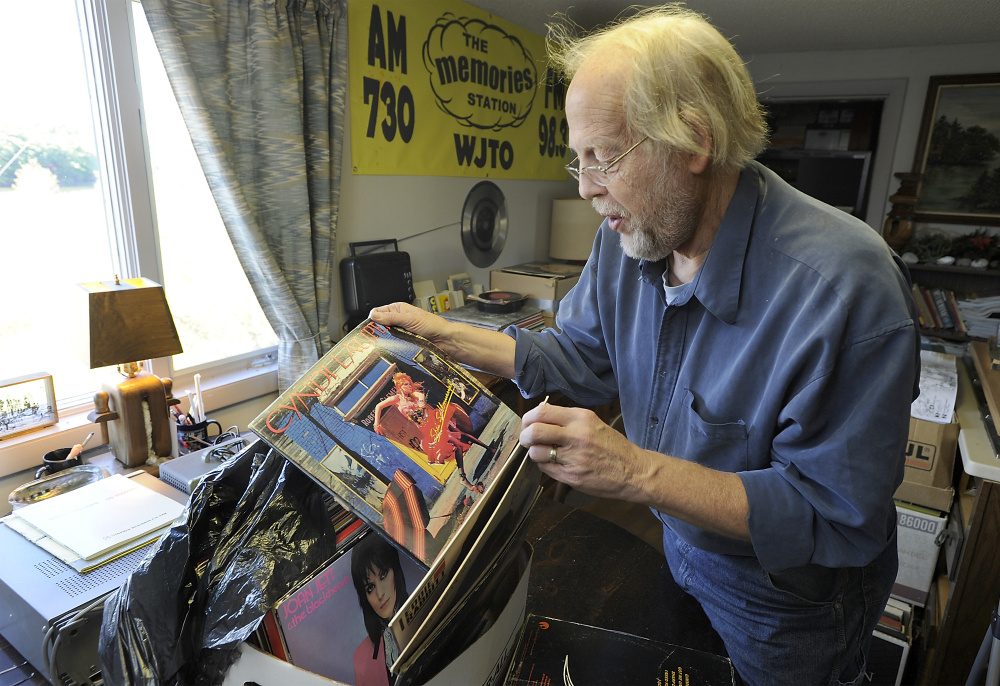 Bob Bittner checks a new donation of albums from a listener and gets excited about ones he does not have.
