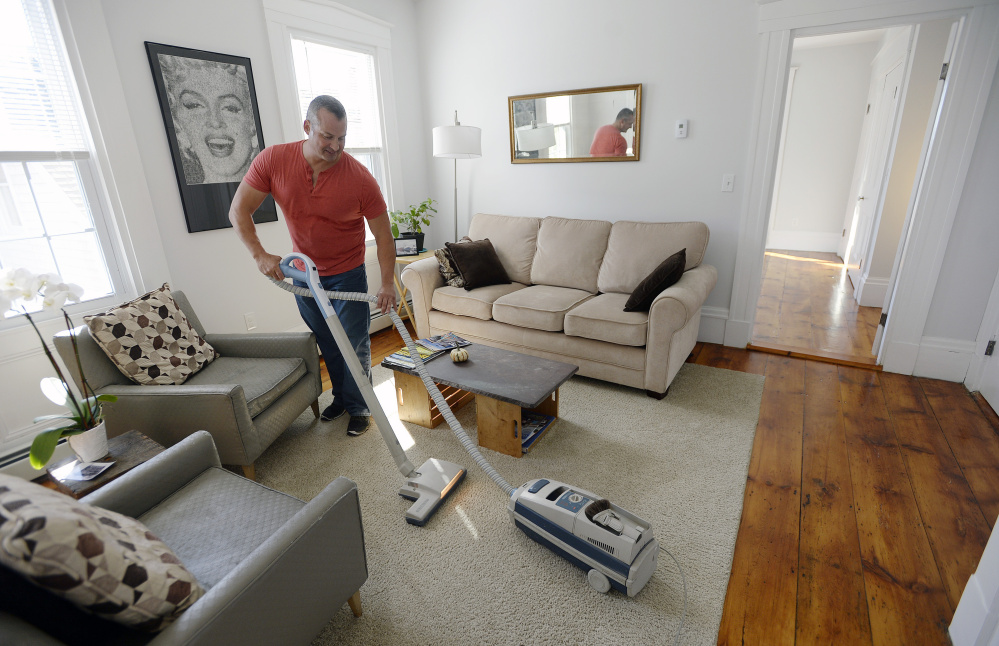 "Gary Wagner vacuums the half of his home he rents out on Airbnb after guests had left Thursday. The West End homeowner started listing the space in July, and says it quickly was booked through October. ""There's a clear demand,"" he said."