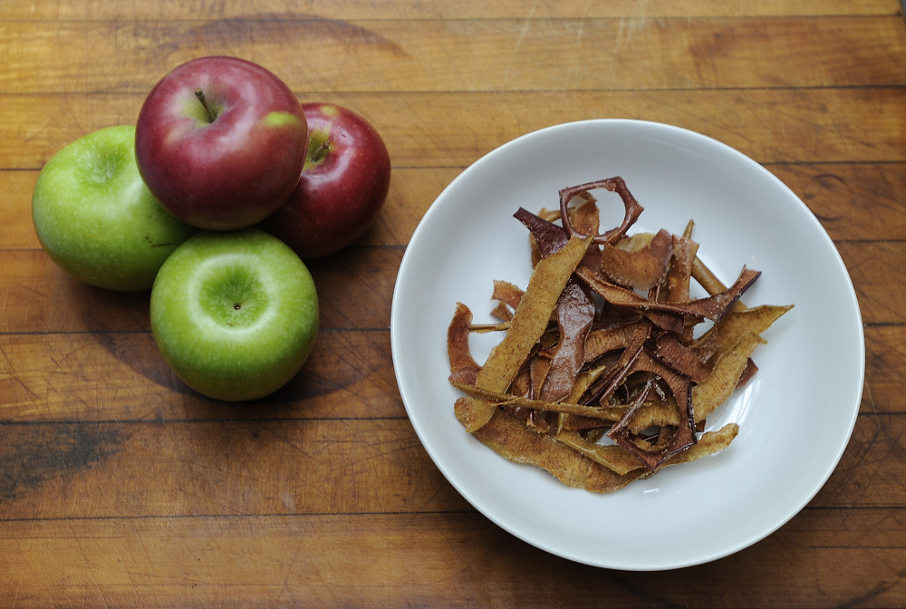 Green Granny Smith and red Macintosh apples sit alongside finished spiced apple peels.