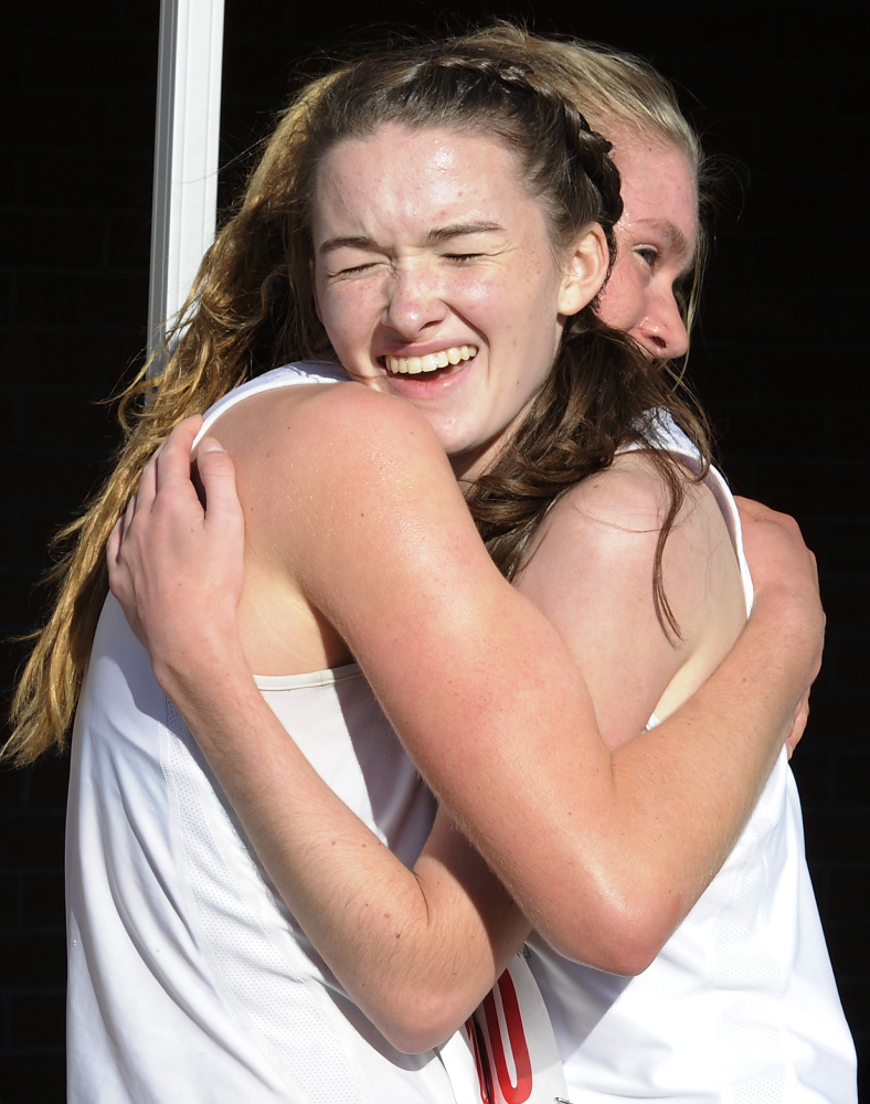 Katherine Legatt-Barr of Greely, left, and teammate Carolyn Todd hug with joy after they finished first and second, respectively,  in the Division 1 portion of the Western Maine Conference championship meet at St. Joseph's College in Standish. Legatt-Barr was timed in 19:19 and Todd in 19:44.