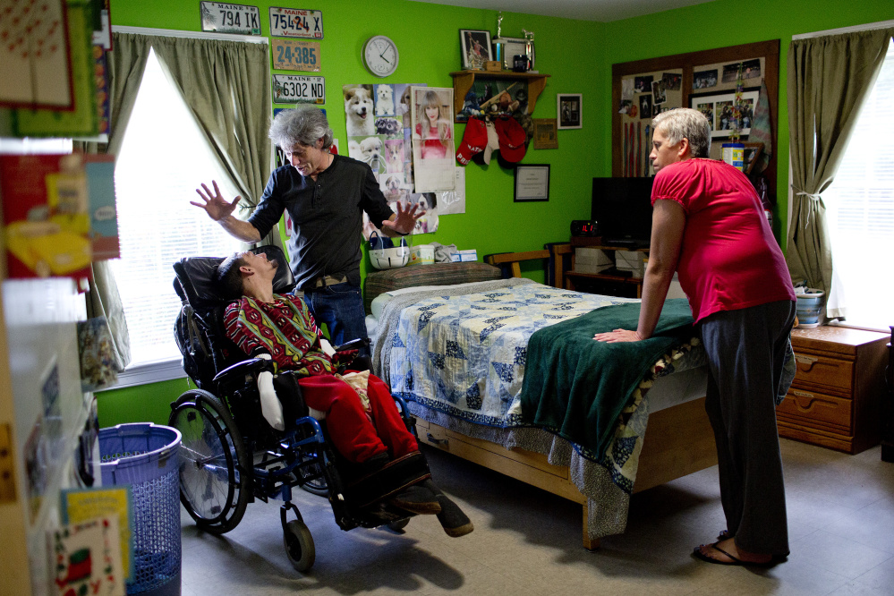 Dan McAllister, program manager at Residential Resources, a group home in Scarborough, talks with client Jerome Gonyer as he and aide Tammy Tapley provide personal care for him. McAllister says that if voters approve a $15 minimum wage on Election Day, it would make it difficult for him to keep his business afloat.  Gabe Souza/Staff Photographer