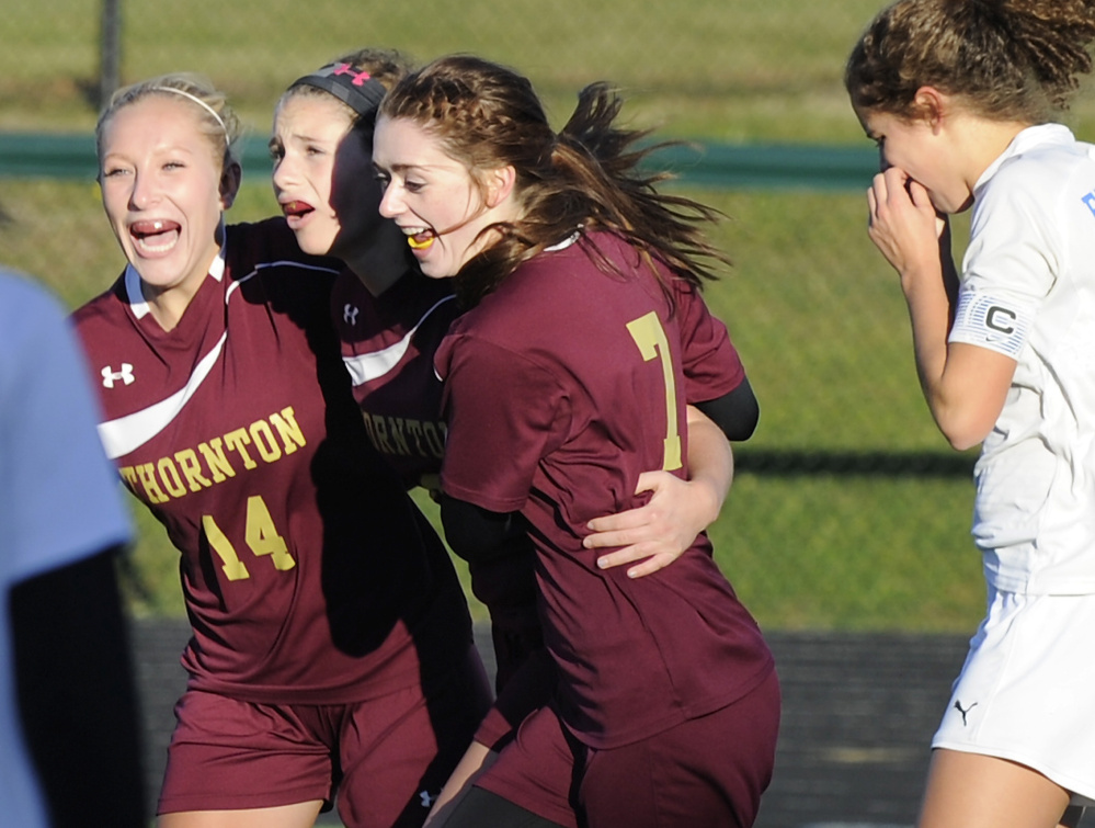Hannah Niles is sandwiched by Thornton Academy teammates Hannah McAlary, left, and Kerrigan Goudreau after scoring Friday in the 1-0 victory against Falmouth. Marcy Kittredge of the Yachtsmen walks away.