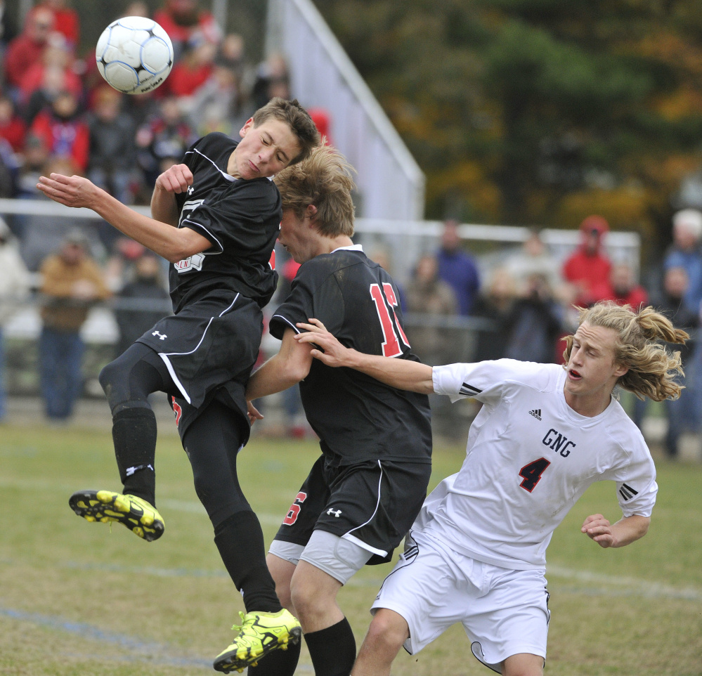 Gus Hunt of Lincoln Academy plays a high ball in front of teammate Nate Masters as Ben Rogers of Gray-New Gloucester is shielded off the play during Gray-New Gloucester's 3-2 win Saturday.