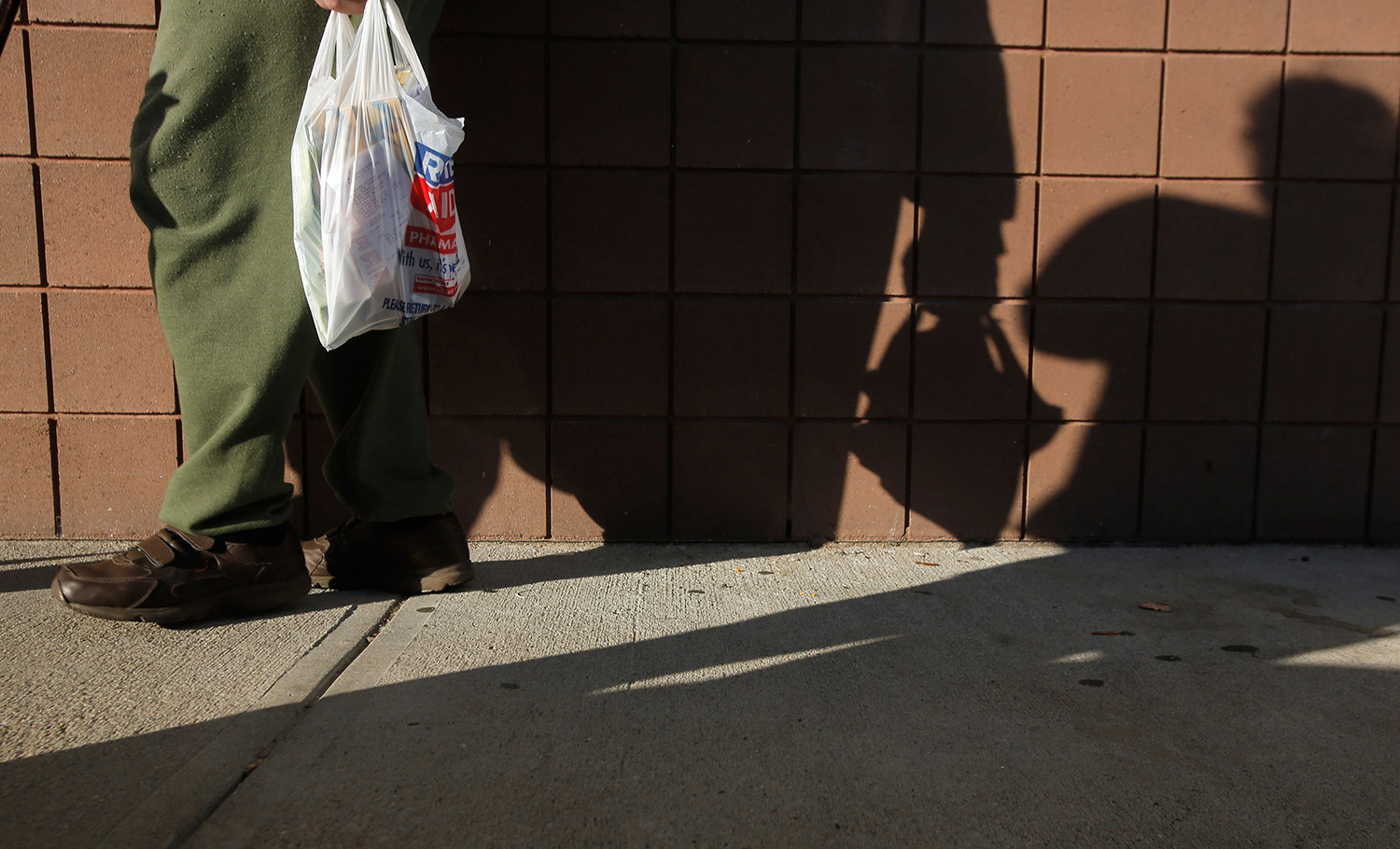 A man carrying a plastic bag out of Rite Aid in York casts a shadow on the wall of the pharmacy on Wednesday afternoon.