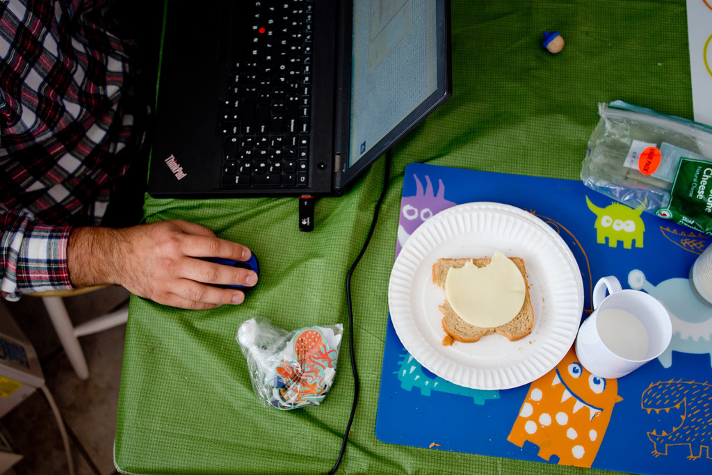 Sean Lavelle tries to get some work done next to a half eaten slice of bread with cheese left from one of his children. For Lavelle, who works virtually from home, being the same motel room as his children during work hours proved distracting.