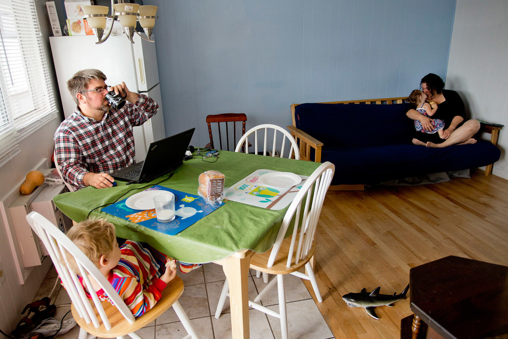 Sean Lavelle takes a sip of his coffee while trying to work from home with his son Graham, 4, at right, wife, Jess, and daughter Mary, 2. Home is a rented motel in Old Orchard Beach that the family lived in for a month while trying to find an apartment in Portland.