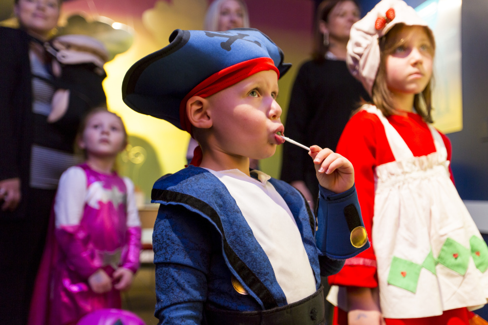 Jake Weisz, center, dressed as a pirate, enjoys a Halloween lollipop during a presentation at the Children's Museum & Theatre of Maine. With Halloween falling on a weekend this year, the museum offered a full slate of activities.