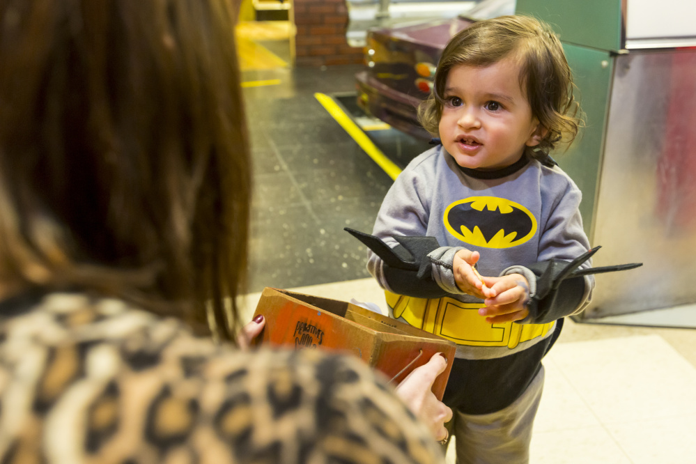 Two-year-old Arnav Thakker, dressed as Batman, receives a toy prize Saturday during a scavenger hunt at the Children's Museum & Theatre of Maine.