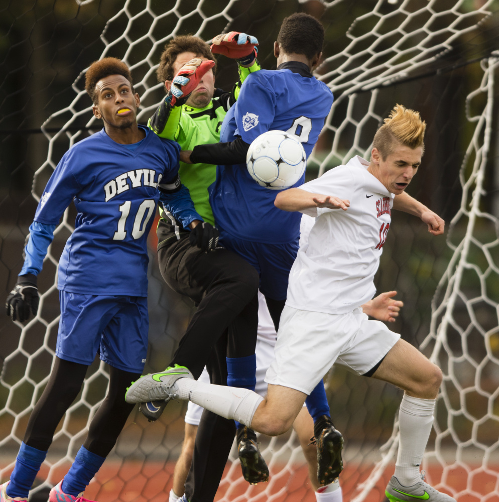 Lewiston goalie Austin Wing contends with heavy traffic while teammates Abdi Shariiff-Hassan, left, and Mohamed Khalid help to deny a threat by Noah Stracqualursi of Scarborough. The Blue Devils gave up seven goals in 18 games this season.