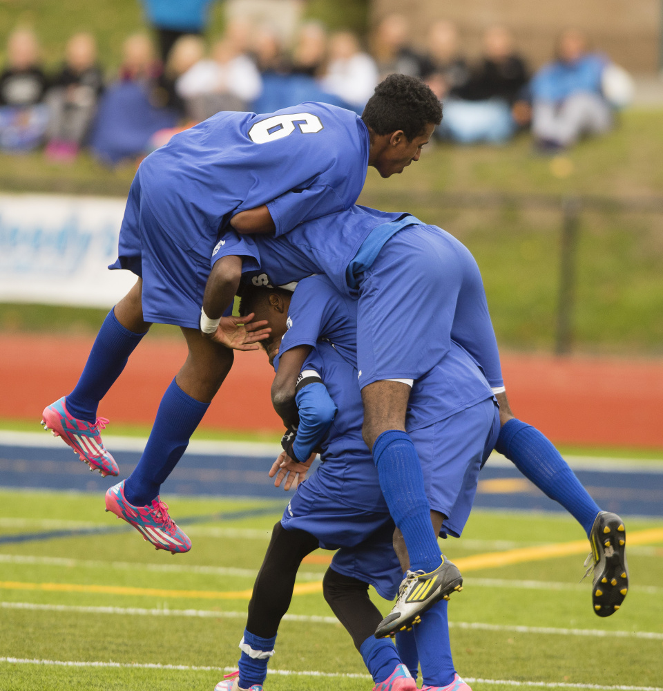 The Lewiston High players pile on Maulid Abdow, whose flip-style throw-in to the box created the scramble that led to an own goal that was the difference in the game.
