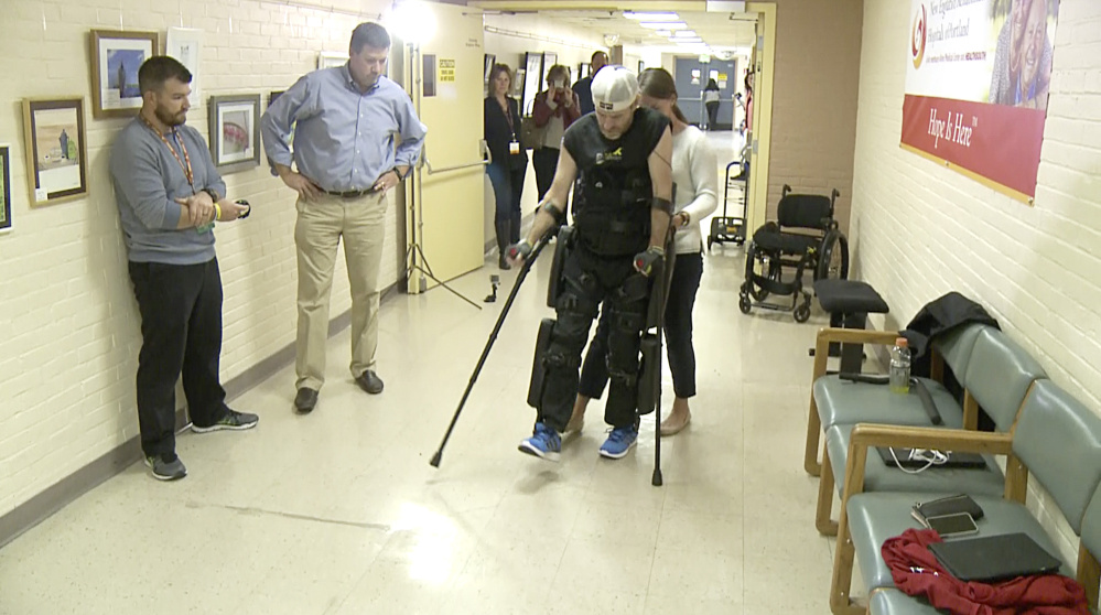 Lauren Peltier of ReWalk Robotics guides Brian Walker at New England Rehabilitation Hospital as he tries out a ReWalk motorized exoskeleton for the first time in Maine, watched by hospital staffers. A small backpack holds the batteries that power the exoskeleton.