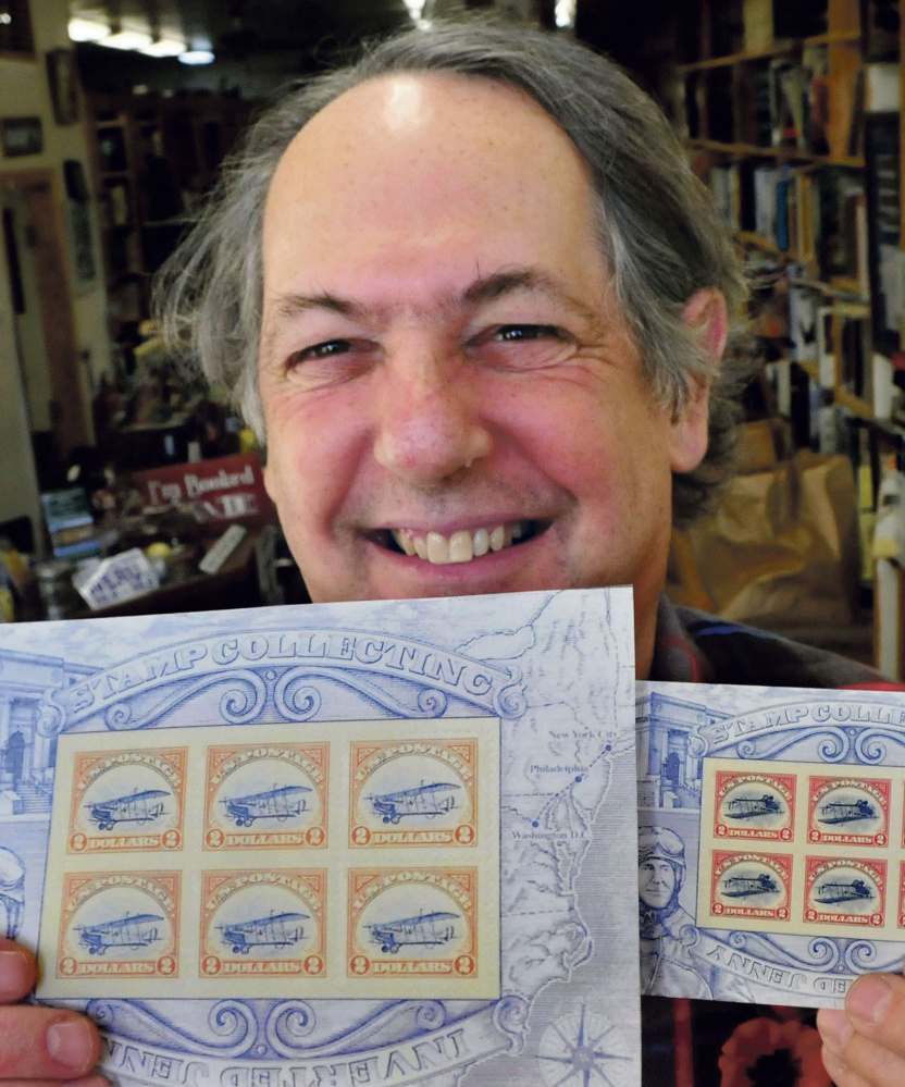 Robert Sezak  holds two versions of the reissued Jenny postage stamps on Monday. The copies at left show an upright Jenny aircraft and could be worth up to $60,000. David Leaming/Morning Sentinel