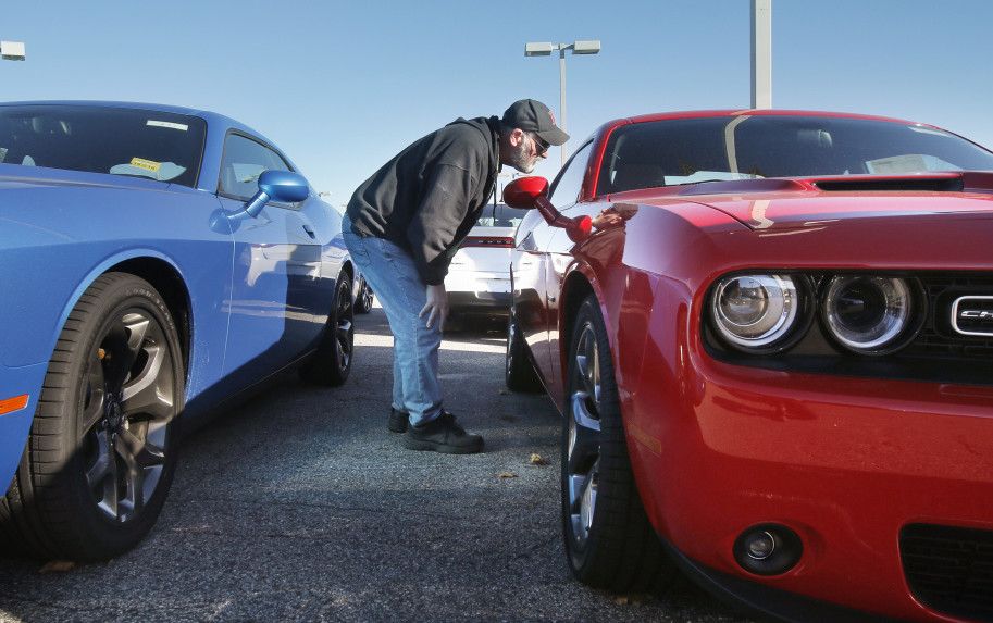 Bob Cournoyer of Lewiston checks out a Dodge Challenger at Lee Auto Mall in Westbrook on Monday. Challengers cost $30,000 to $40,000, representing some of the pricier models that Mainers have been leaning toward in 2015.