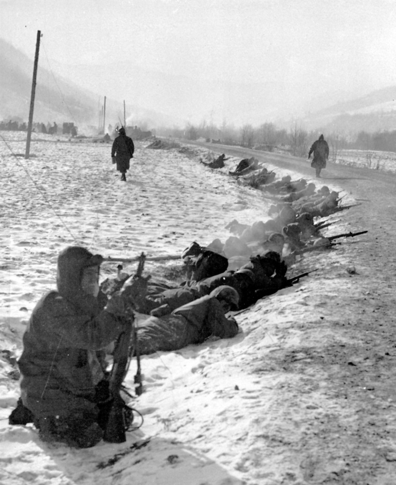 Marines lie in the snow with rifles ready at a curve in a road in the Chosin Reservoir area on Nov. 29, 1950. Associated Press via U.S. Marine Corps